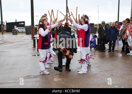 Morris dancers perform at the Stade on the seafront at Hastings, England during the annual Jack In The Green festival - Stock Photo