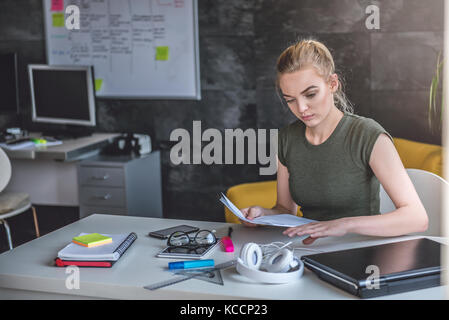 Young business woman doing paperwork in the office - Stock Photo