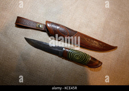 A fixed blade damascus knife and leather sheath displayed on a burlap background - Stock Photo