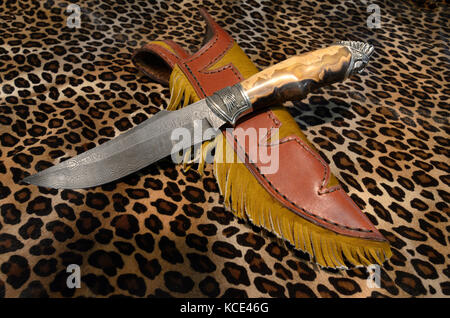 A fixed blade damascus knife and leather sheath displayed on a leopard like skin background - Stock Photo