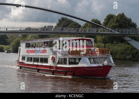 Passengers enjoy a sunny summer trip, sailing on the River Ouse, aboard a City Cruises boat, passing near the Millennium - Stock Photo