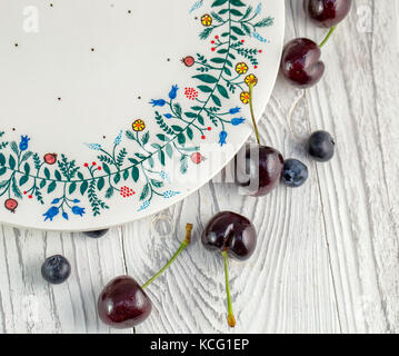 Blueberries and cherries next to the plate with ornament on the white wooden background - Stock Photo