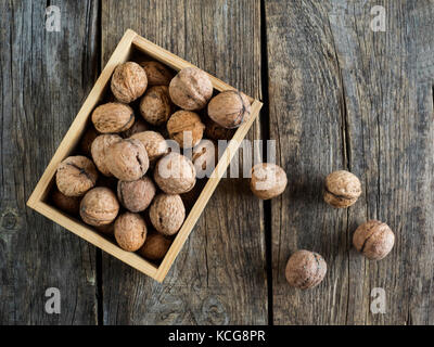 walnuts in a wooden box on an old weathered wooden table - Stock Photo