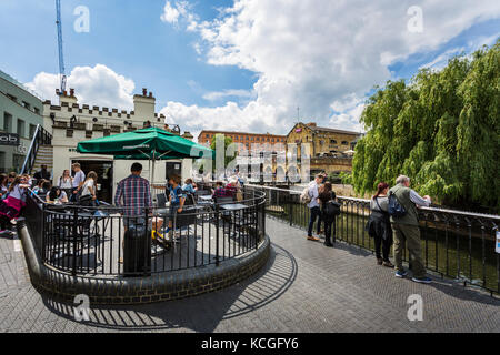 Wide angle picture from Camden Lock in a sunny day with clouds, trees, many people by the canal in London. - Stock Photo