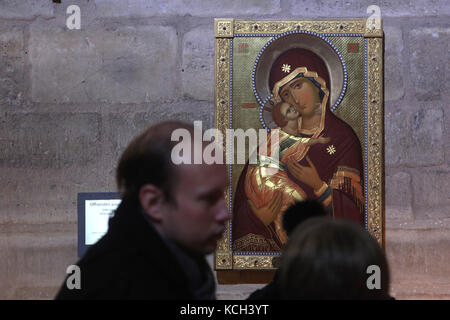 Visitors in front of the icon of the Theotokos of Vladimir in the Notre-Dame Cathedral (Notre-Dame de Paris) in - Stock Photo