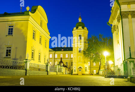 The evening view on courtyard of Pochaev Lavra with water tower in the middle, Pochaev, Ukraine - Stock Photo