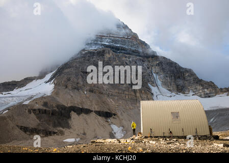 A climber scopes the summit while at the R.C. Hind hut below Mt. Assiniboine - Stock Photo