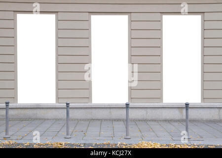 Three blank vertical mockups on a building wall. Autumn street. Front view - Stock Photo