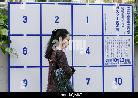 A woman walks past a poster board erected specifically for candidates' posters for the upcoming October 22 general - Stock Photo