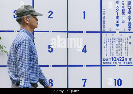 A man walks past a poster board erected specifically for candidates' posters for the upcoming October 22 general - Stock Photo