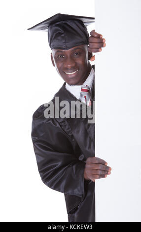 Young Graduation Man Holding Empty Billboard Over White Background - Stock Photo