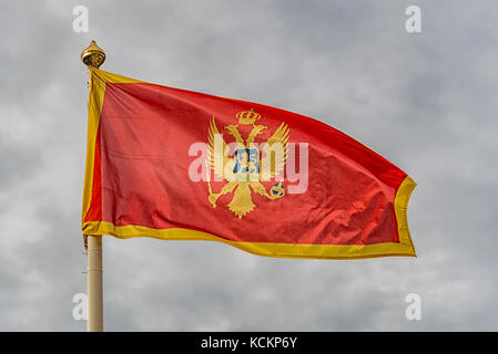 The flag of Montenegro fluttering in the wind against a cloudy sky background. - Stock Photo