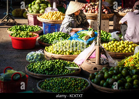 A female market stall vendor in a conical hat selling limes in Dong Ba Market, Hue - Stock Photo