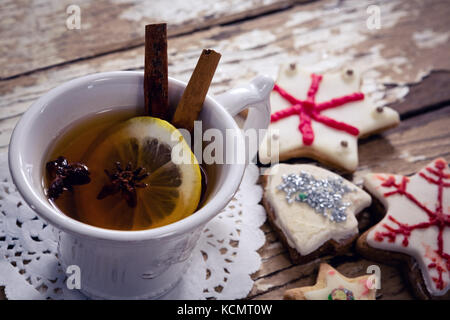 Close-up of tea, spices and cookies on wooden plank - Stock Photo