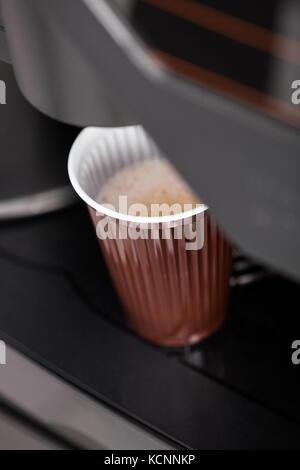 Coffee maker pouring hot espresso coffee in a glass - Stock Photo