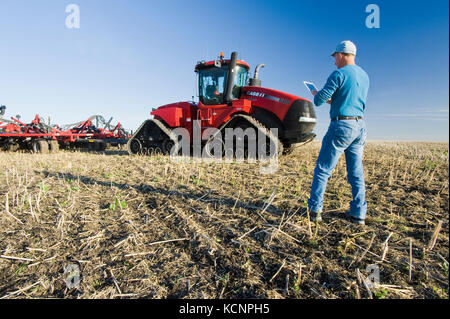 farmer using a tablet in front of a tractor and air seeder planting winter wheat in a zero till field containing - Stock Photo