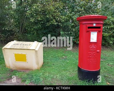 A red Royal Mail pillar box next to a yellow grit salt bin in England, October 2017 - Stock Photo