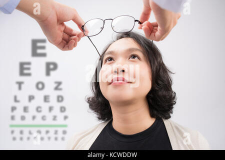 New glasses. Optometrist giving asian woman eyeglasses to try - Stock Photo