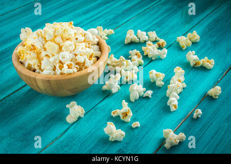 Popcorn in wooden plate on a blue background. - Stock Photo