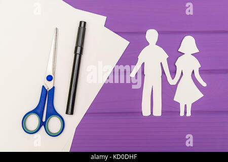 Paper silhouette of man and woman holding hands - Stock Photo