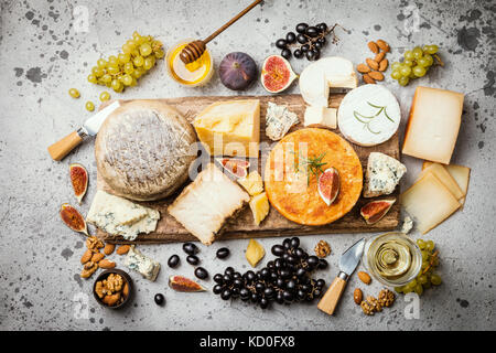 various types of cheese on wooden cutting board, top view - Stock Photo