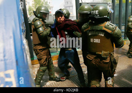 Santiago, Chile. 09th Oct, 2017. A man gets arrested during a march in Santiago, Chile, 09 October 2017, for the - Stock Photo