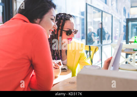 Women on city break at outdoor cafe, Milan, Italy - Stock Photo