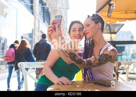 Women on city break at outdoor cafe taking selfie, Milan, Italy - Stock Photo