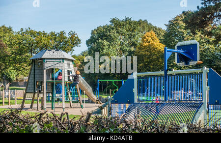 Children's playground / play area, with two children on a climbing frame on a warm sunny day early autumn. Gunnersbury - Stock Photo