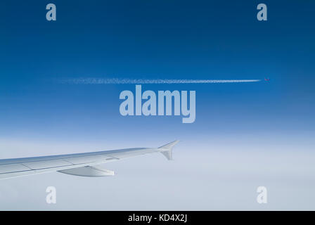 Jet Wing and Passing Plane with Contrails - Stock Photo