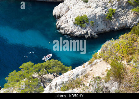 Calanque de Sugiton, boat in an inlet, people swimming in azure sea water, Calanques National Park, France - Stock Photo