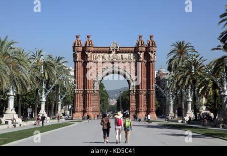 Tourists walking to The Arc de Triomf .Arco de Triunfo.Triumphal arch in Barcelona Catalunya Spain - Stock Photo
