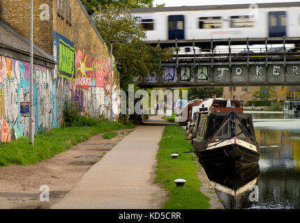 A train on the the Great Eastern line out of Liverpool Street crosses the Regents Canal at Mile End - Stock Photo