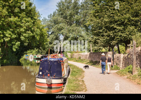 7 July 2017: Bradford on Avon, Somerset, England, UK - Couple with dog walking on the tow path beside a row of narrowboats - Stock Photo