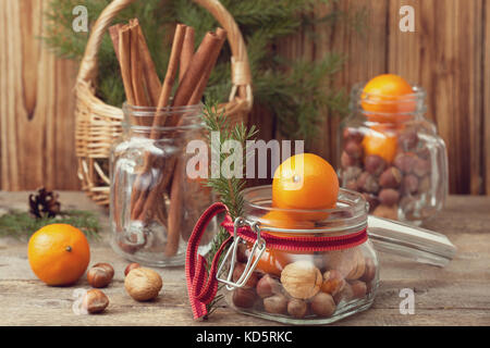 Christmas gift in a glass jar: walnuts, hazelnuts, tangerines on the old wooden background - Stock Photo