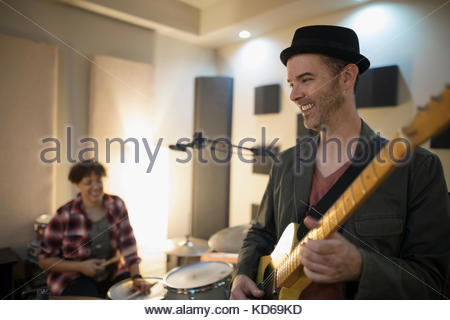Smiling male guitarist playing in recording studio - Stock Photo