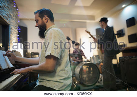 Male pianist writing music, playing in recording studio - Stock Photo
