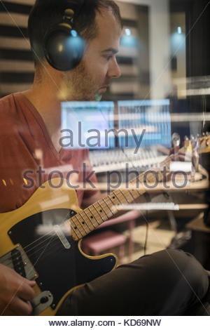Focused male guitarist with headphones playing in recording studio - Stock Photo