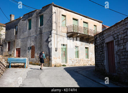 A female hiker walking past abandoned houses along a steep street in the village of Kioni on Ithaka in the Greek - Stock Photo