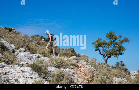 A woman walking near the village of Anogi to the summit of Mount Nirito the highest point on the island of Ithaka - Stock Photo