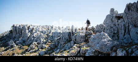 A woman walking on the jagged summit of Mount Nirito the highest point on the island of Ithaka in the Ionian Sea - Stock Photo