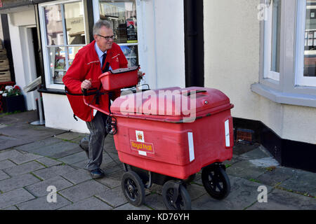 Postman pushing cart making deliveries on rounds in small English market town of Thornbury, South Gloucestershire - Stock Photo