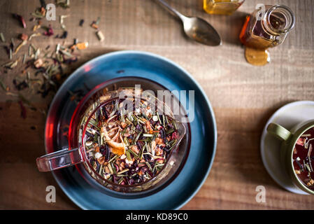 Beautiful tray of tea being prepared. Overhead showing texture of loose leaf tea floating in glass teapot with honey - Stock Photo