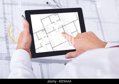 Close-up Of Male Architect Analyzing Blueprint Over Digital Tablet - Stock Photo