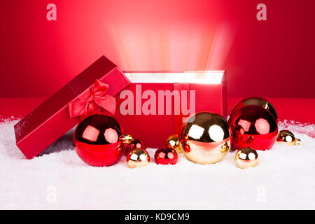 Opened Gift Box With Christmas Baubles On Red Background - Stock Photo