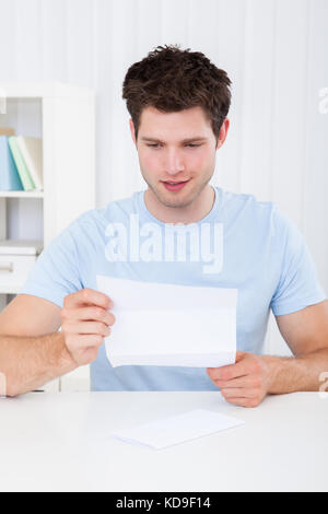 Happy Young Man Reading Paper Holding In Hands - Stock Photo