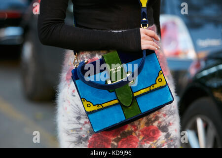 MILAN - SEPTEMBER 21: Woman with Prada velvet bag in green, blue and yellow colors before Prada fashion show, Milan - Stock Photo