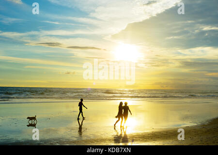 People walking on tropical Bali ocean beach at sunset. Indonesia - Stock Photo
