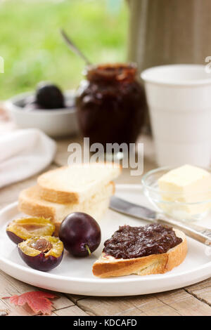 Toasts with plum chocolate jam and cocoa. Breakfast in the garden. Rustic style, selective focus. - Stock Photo