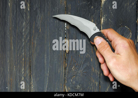 A man holds a knife in his right hand. Knife for attack. Black background. - Stock Photo